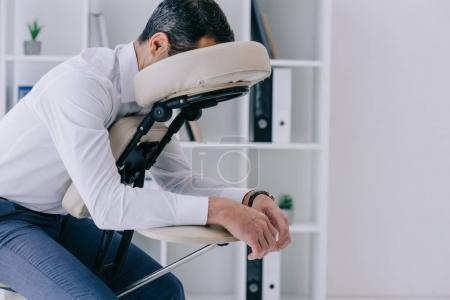Foto de Hombre de negocios sentado en la silla de masaje en la oficina - Imagen libre de derechos