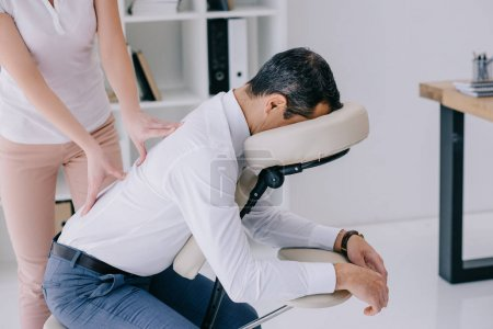 masseuse doing back massage on seat at office