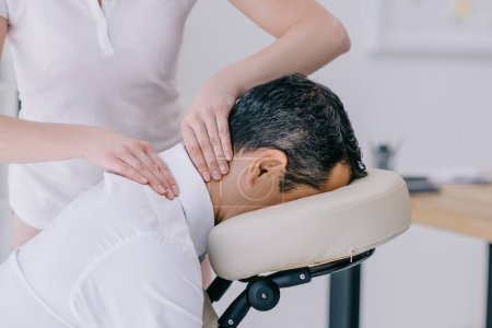 close-up shot of masseuse doing neck massage for businessman