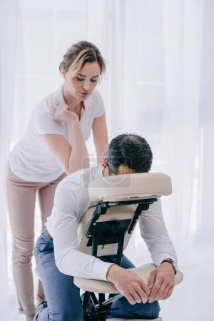 Photo for Professional masseuse doing seated back massage for businessman - Royalty Free Image