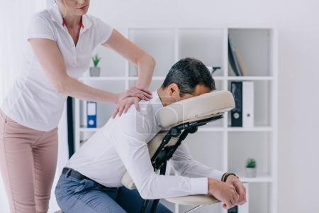 Photo for Beautiful adult masseuse doing seated massage for businessman - Royalty Free Image