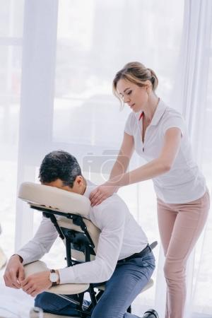 beautiful adult masseuse doing office massage for businessman