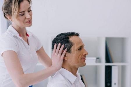 side view of masseuse doing head massage for handsome mature businessman