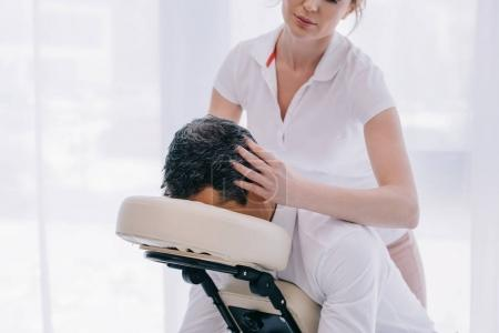attractive masseuse doing head massage for businessman