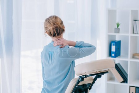 rear view of businesswoman with neckpain sitting on massage chair