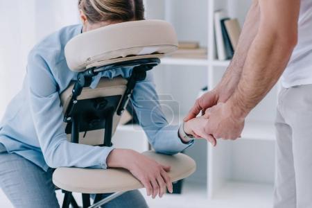 Photo pour Masseur faire massage des mains pour femme d'affaires au bureau - image libre de droit