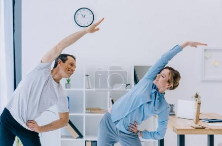 Photo for Businesswoman doing side bend with trainer at office - Royalty Free Image