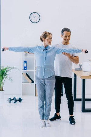 beautiful businesswoman and her personal trainer working out with dumbbells at office