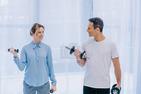 businesswoman and her personal trainer working out with dumbbells at office