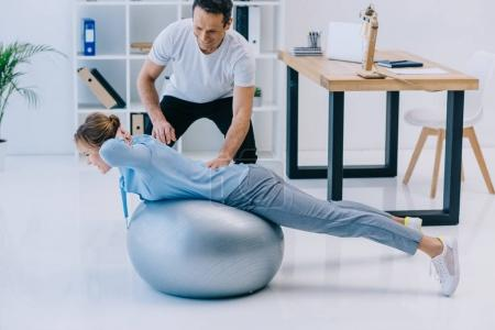 side view of businesswoman doing hyperextension exercise on fit ball with trainer at office