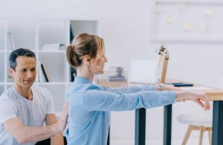 businesswoman working out with personal trainer at office