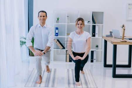 businessman with his trainer practicing yoga in Crescent Lunge pose at office