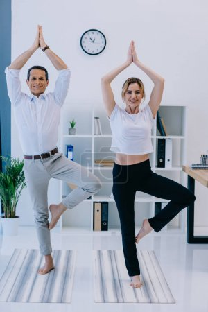 businessman with his trainer practicing yoga in tree pose at office