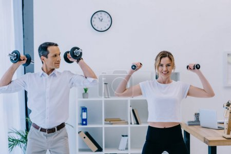 happy mature businessman with his personal trainer working out with dumbbells at office