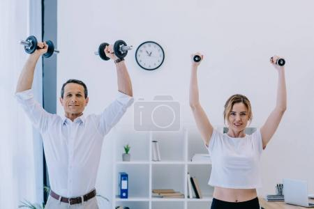 businessman with his female personal trainer working out with dumbbells at office