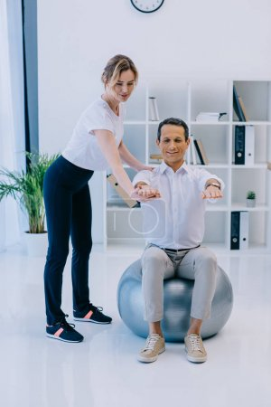 happy mature businessman doing exercise while sitting on fit ball with female personal trainer