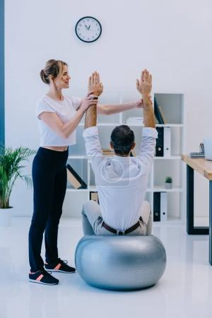 businessman doing exercise while sitting on fit ball with female personal trainer