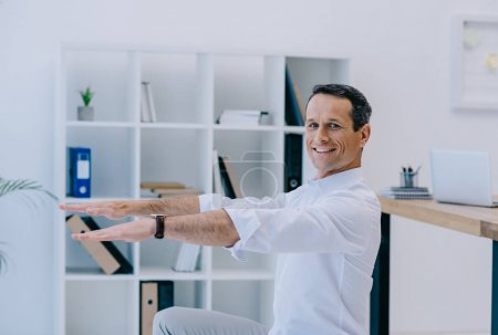 happy mature businessman doing squats at office