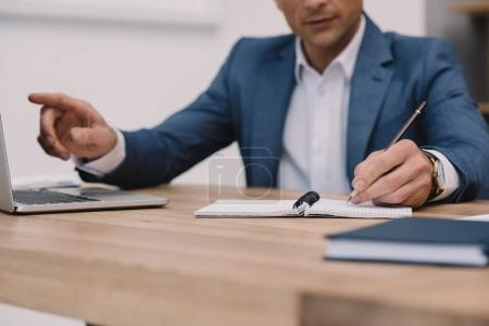 cropped shot of businessman making notes while using laptop at workplace