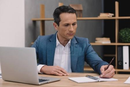 focused mature businessman making notes at workplace