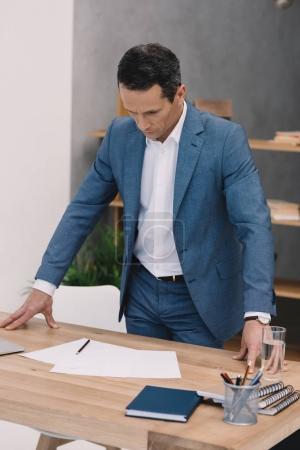 Photo pour Concentré d'homme d'affaires, lisez des documents sur son bureau au bureau - image libre de droit