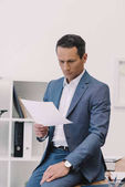 handsome businessman reading business paper at office