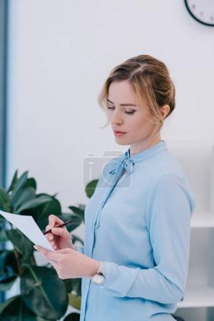 Photo for Attractive businesswoman with pencil reading document - Royalty Free Image