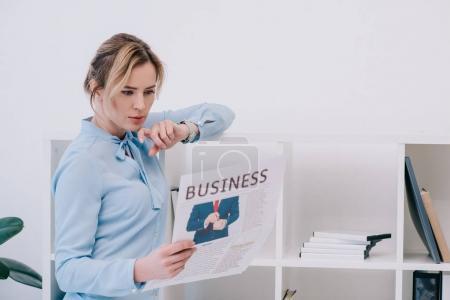 Photo pour Femme d'affaires concentrée lisant le journal au bureau - image libre de droit