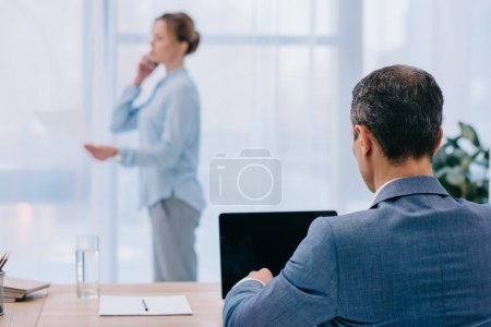 businessman working with laptop while his colleague talking by phone at office