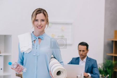 businesswoman with fitness equipment standing at modern office while her colleague working with computer
