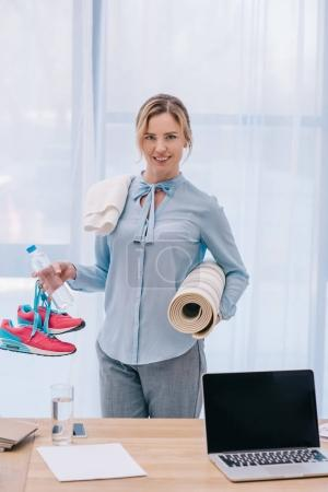 sporty businesswoman with fitness equipment at office