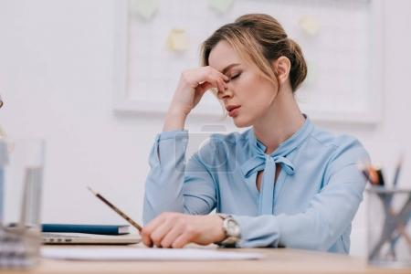 Photo for Exhausted adult businesswoman sitting at workplace in office - Royalty Free Image