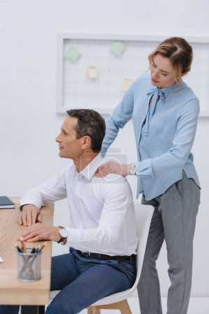 businessman working with laptop at workplace while his secretary doing massage for him