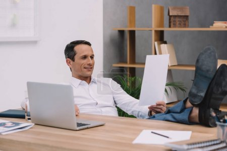 handsome smiling businessman reading document at workplace at office