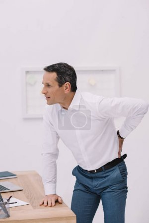 handsome mature businessman with painful backache at office