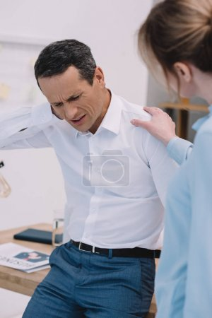businessman has neck pain while his colleague trying to help him at modern office