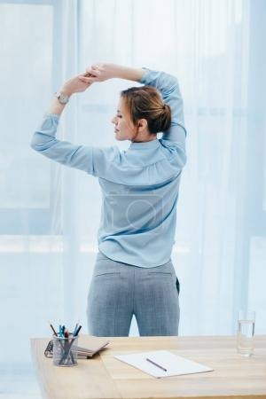rear view of attractive businesswoman doing morning gymnastics at office