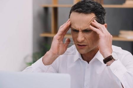 mature businessman with painful migraine trying to work at office