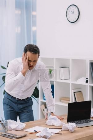 suffering businessman with painful migraine at office