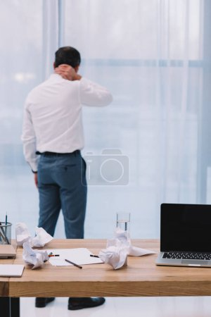 mature businessman with neck pain at office with messy workplace on foreground