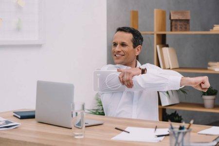 Photo pour Heureux homme d'affaires mature échauffer son épaule tout en travaillant au bureau - image libre de droit