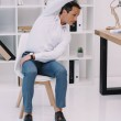 Mature businessman doing side bend on chair at off...