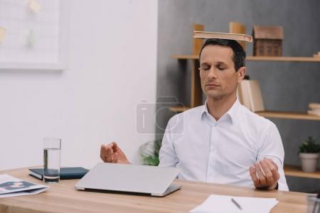 Photo pour Homme d'affaires calme méditer avec le livre sur la tête au bureau - image libre de droit