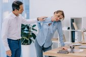 attractive businesswoman has back pain while her colleague trying to help her at office