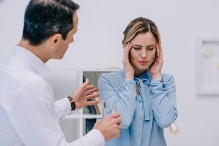 businesswoman has headache while her colleague trying to help her at office