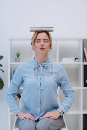 beautiful businesswoman meditating with book on head at office