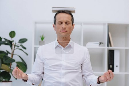 handsome businessman meditating with book on head at office