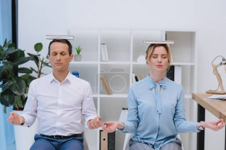 businesspeople meditating with books on head at modern office