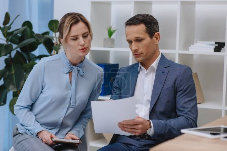 Photo for Businesspeople discussing contract together at office - Royalty Free Image