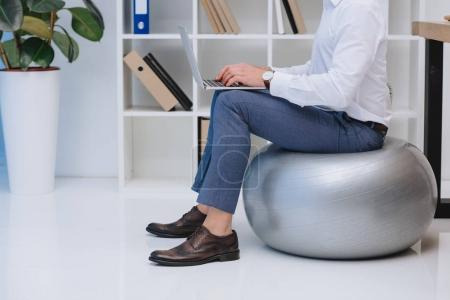 cropped shot of businessman working with laptop while sitting on fit ball
